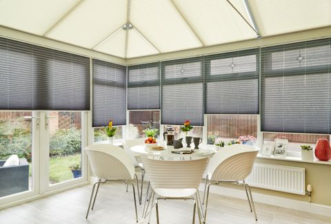 Relaxing dining area in a conservatory fitted with Sand Pleated roof blinds and grey Pleated side blinds