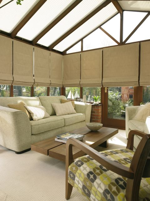 warm and cosy living area in a conservatory with cream sofas and white pleated Conservatory roof blinds