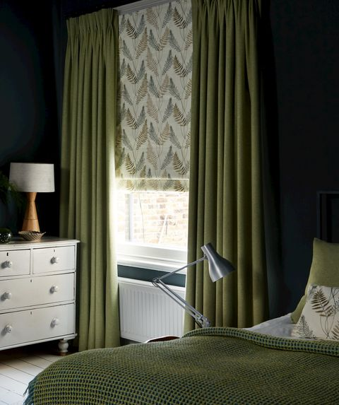 Bedroom window with green curtains and fern motif Roman blinds
