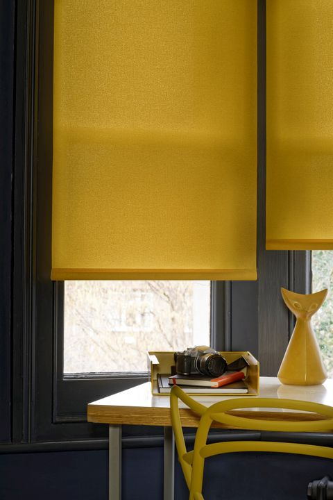 Close up detail of mustard Roller blind in bay window