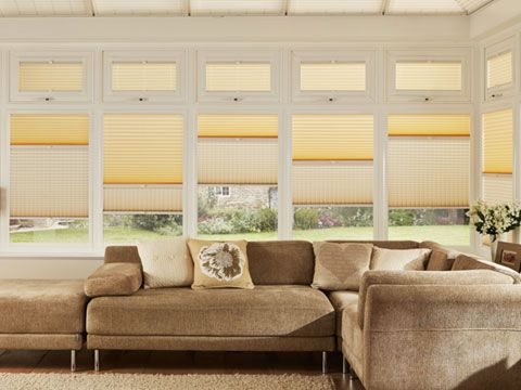 Cosy conservatory with taupe sofa and cream transition blinds