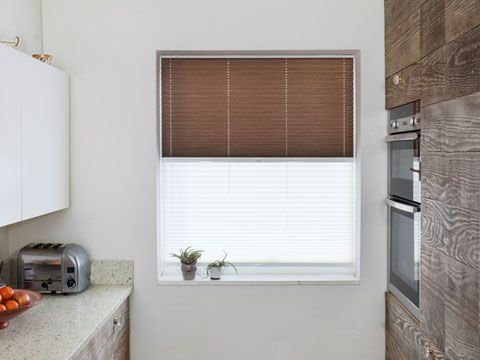 Small galley kitchen with single window dressed with brown and white transition blinds