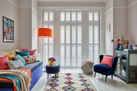 Living room with full height shutters at french doors