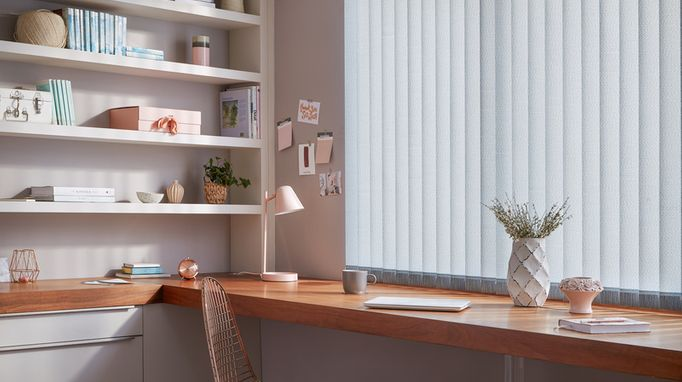 Off-white Vertical blinds in a home office. The blinds are above an oak desk