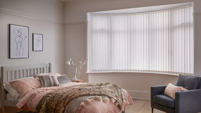 white vertical blinds in a bedroom window