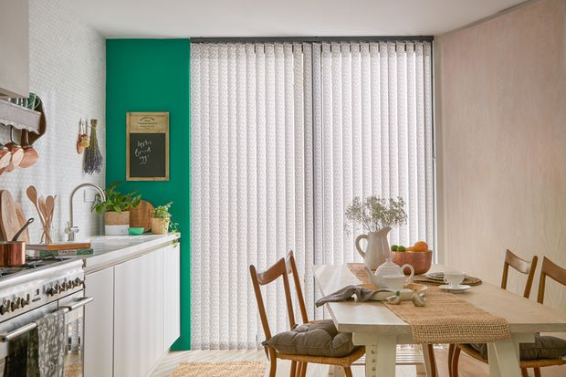 light grey patterned vertical blinds in a kitchen window