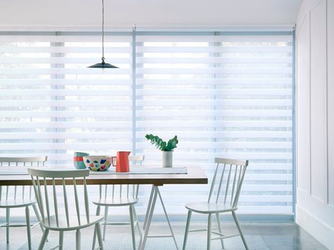 Dining room table with wide windows in the background with day and night roller blinds