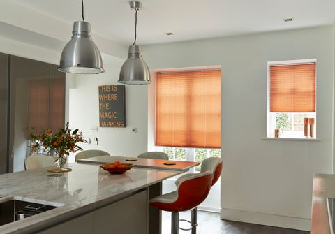 Modern industrial style kitchen with statement pleated blinds in orange rust colour