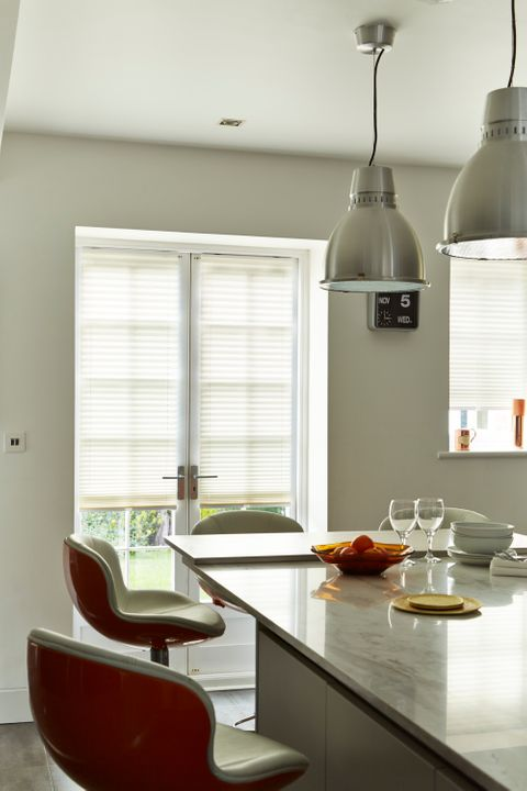 Modern kitchen breakfast bar with french doors dressed with pleated blinds