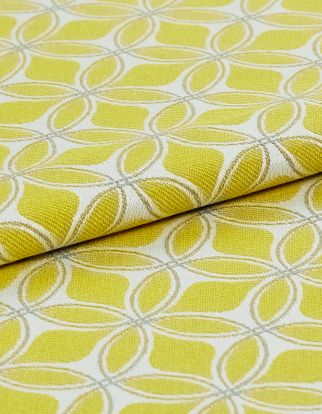 white fabric decorated in yellow with a geometric design that repeats across the material