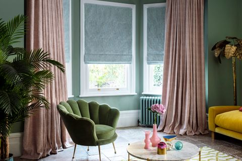 pink curtains over grey roman blinds in green painted living room
