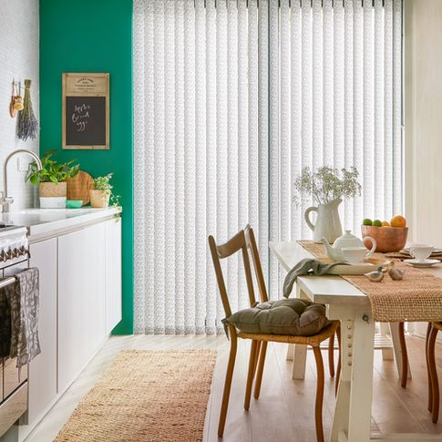 Modern kitchen diner with statement green walls and full length window with patterned vertical blinds