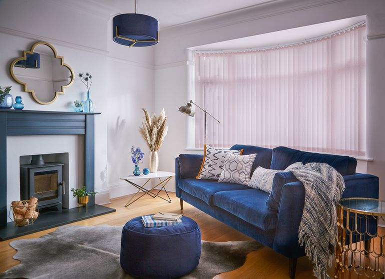 Modern luxe living room with royal blue decor and pale pink vertical blinds