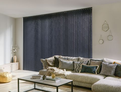 Modern luxe living room with plush cushions with gold accents and charcoal black vertical blinds