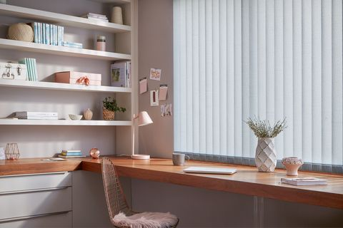 Modern home office with build in desk and shelves and windows dressed with pale blue vertical blinds