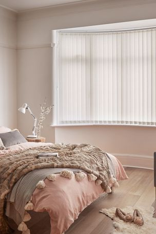Minimal luxe bedroom with soft furnishings and a bow window dressed with light cream vertical blinds
