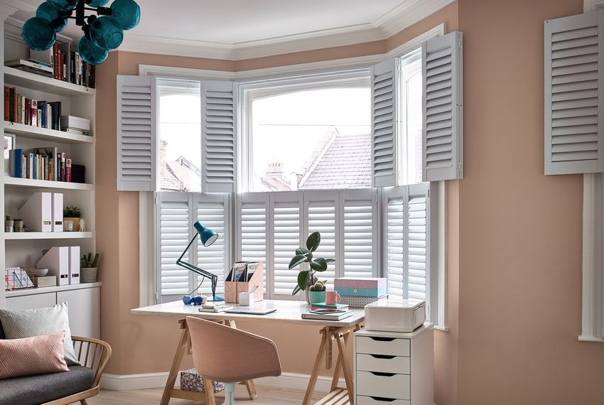 White tier-on-tier Shutters in a bay window in a beige-themed office. There is a desk in front of the shutters.