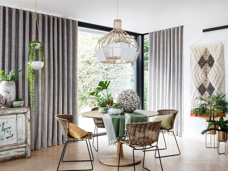 Modern bohemian dining area with grey dining room curtains