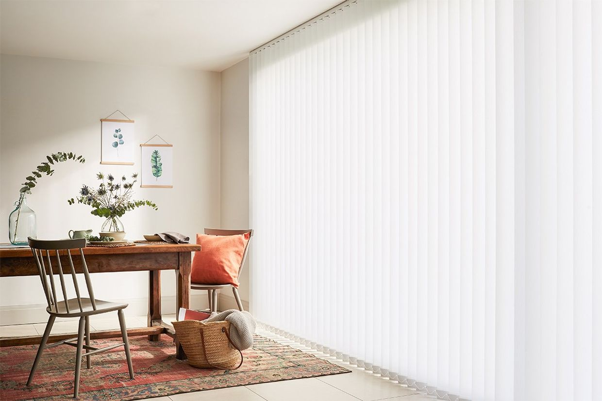 Rustic dining room with large window dressed with full length white vertical blinds