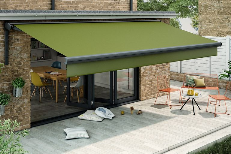 Verona Pique Green Awning hanging over a garden patio with table and chairs