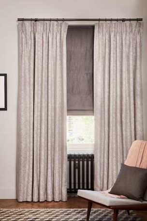 Small cosy room with light-coloured curtains in echo zinc fabric layered with a grey roman blind