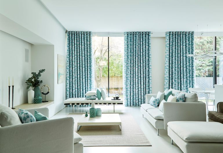 Blue floral prints curtains in Honesty Mist fabric in neutral living room with sofas and matching fabric cushions
