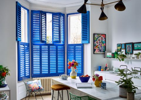 A kitchen consisting of a dining table and chairs, flowers, a fruit bowl and a window containing ultra blue shutters