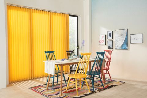 Dining room with sliding glass door dressed in  bright yellow vertical blind
