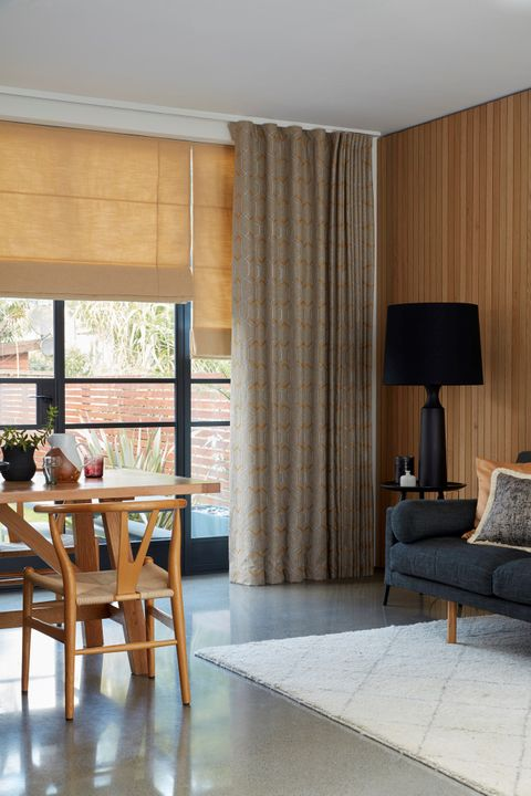 Open Plan Living Space with Wave Curtains in Verve Golden Wheat Fabric paired with Lindora Gold Roman Blind
