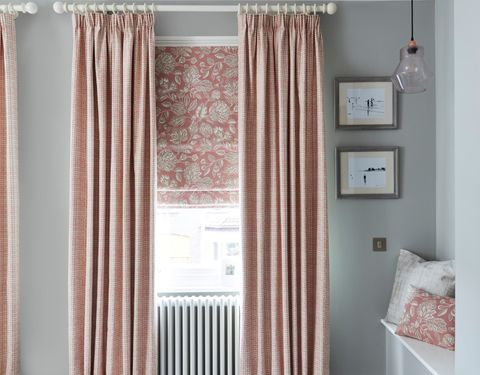 peach coloured eyelet curtains over floral roman blinds in bedroom