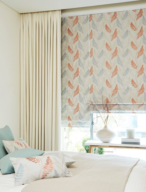 Florally decorated roller blinds matched withe cream coloured curtains are fitted to a large window in a bedroom decorated in soothing colours