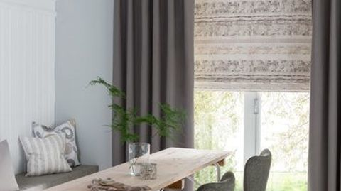 Cream coloured roman blind with a repeating pattern in neutral colours and paired with grey curtains, both are fitted to a bi fold door in a dining room that has a dining table and a bench built into the wall on the left
