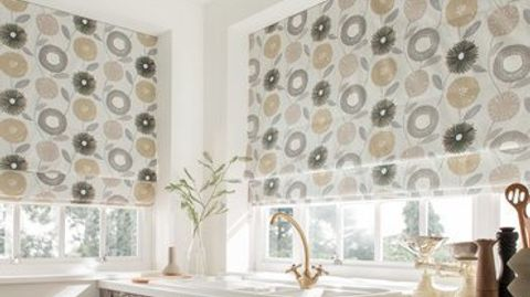 Large white roman blinds with repeating floral designs in grey and beige are fitted to wide rectangular windows in a bathroom decorated in white