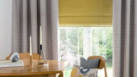 Yellow coloured roman blind paired with grey patterned curtains in a dining room with a wooden kitchen table and chairs