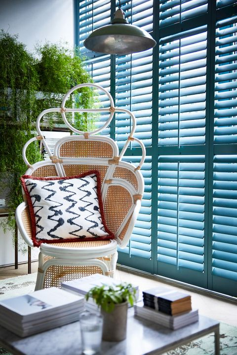 Blue full height shutters fitted to a large rectangular window in a living room featuring a wicker chair and coffee table