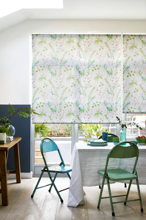White and tropical patterned roller blinds fitted to door windows in a dining room with a dining table and chairs