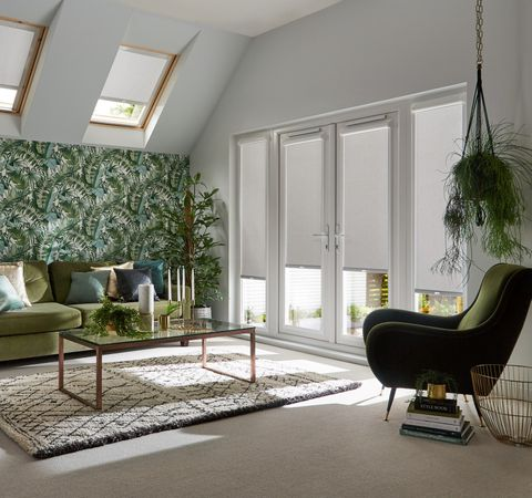 Silver coloured roller blinds fitted to a door window and two small skylight windows in a living decorated in green and white