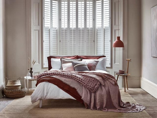 Tall tier-on-tier shutters covering a luxurious bedroom window. The shutters are white, with the louvres closed in the bottom half