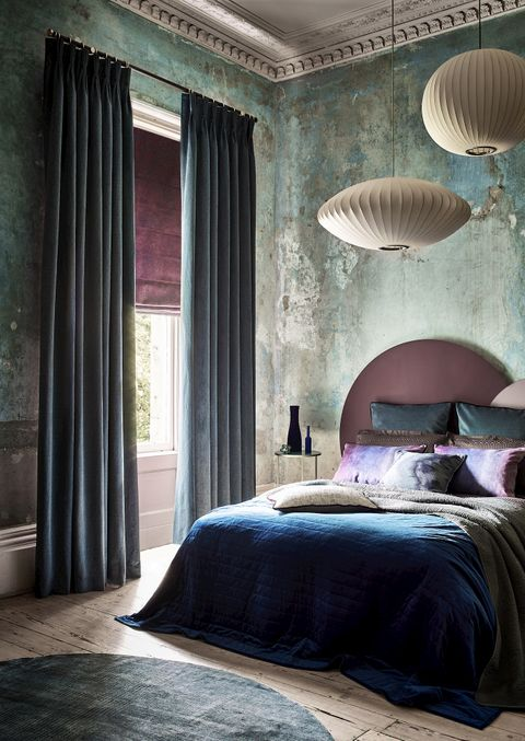 A faded glamour bedroom featuring blue curtains over a purple Roman blind at a single window