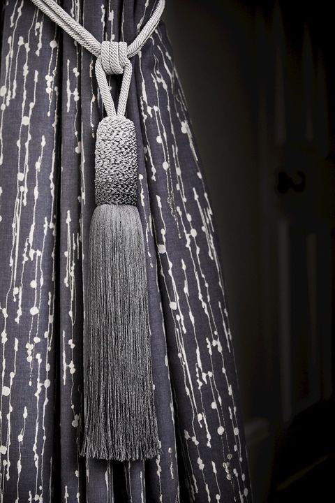 Close up detail of grey and silver curtain with grey ombre tassel tie-back