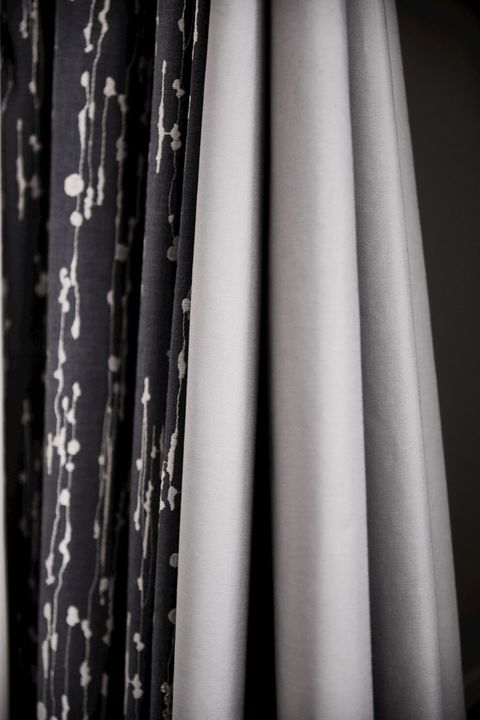 Close up detail of grey and silver curtain with complementary grey blackout curtain lining