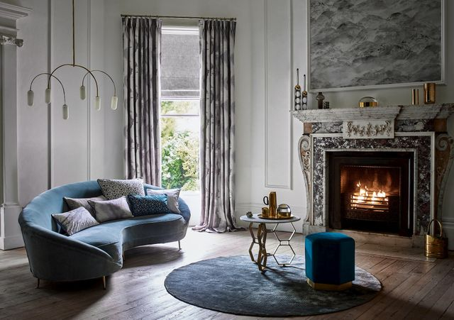 Stately living room with eroded effect curtains over a textured Roman blind at a single window