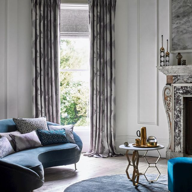 Living room with curved velvet sofa and a single window dressed with printed curtains layered over a Roman blind