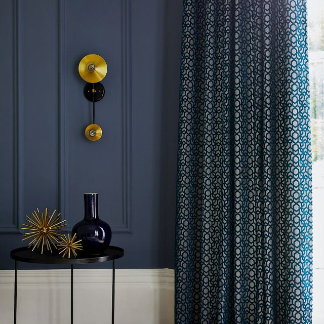 Close up detail of living room with full length curtain and side table