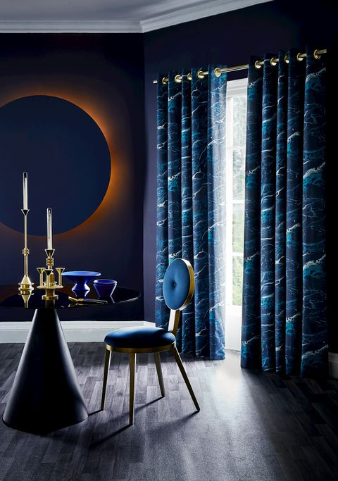 Opulent dining room featuring blue printed curtains over French doors