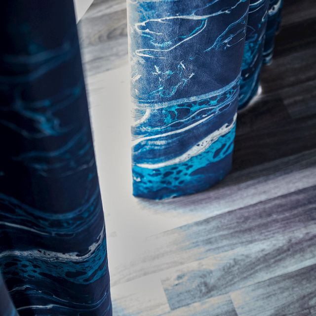 Close up detail of blue and white curtain hem touching grey wooden floor