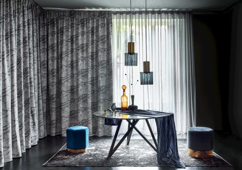 Dining room with grey printed curtains layered over a sheer grey voile curtain