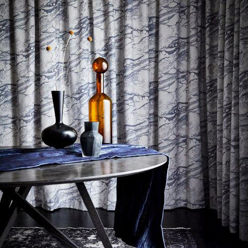 Close up detail of dining room table with marbled velvet curtains behind
