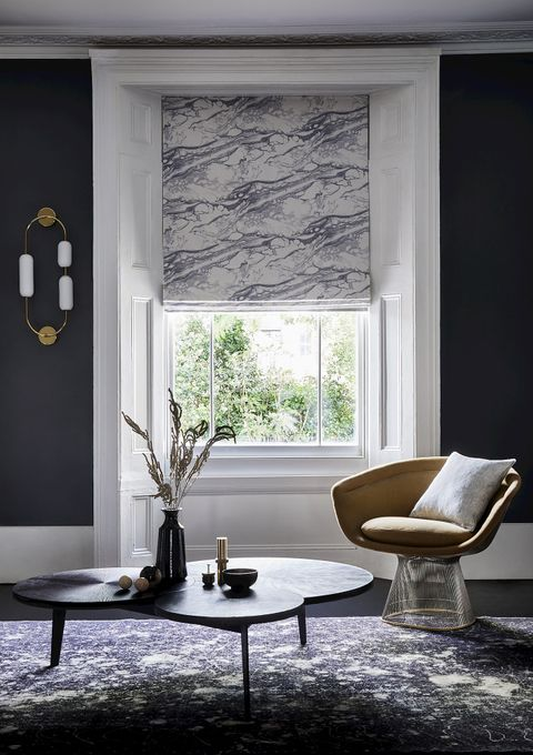 Living room with grey marbled Roman blind at single window