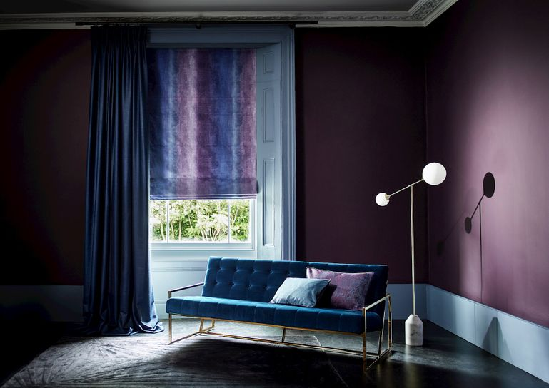 Living room with velvet sofa and single window dressed with curtains layered over a Roman blind